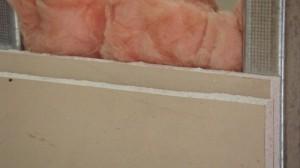 Укладка минеральной ваты для звукоизоляции гипсокартонной стены.